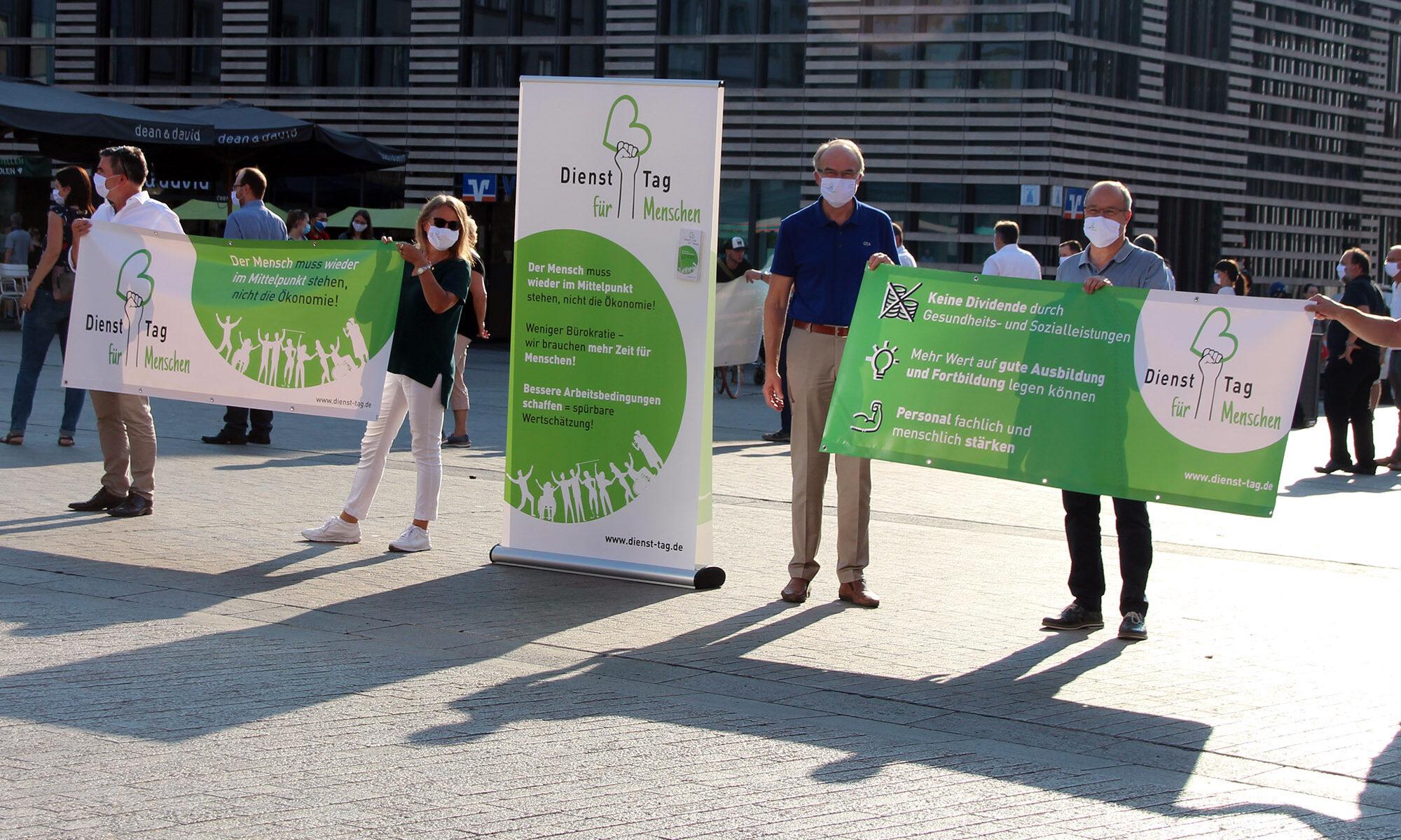 Auf dem Unteren Markt in Würzburg stehen Menschen mit Mundnasenschutz und halten Banner mit Demonstrationsforderungen.